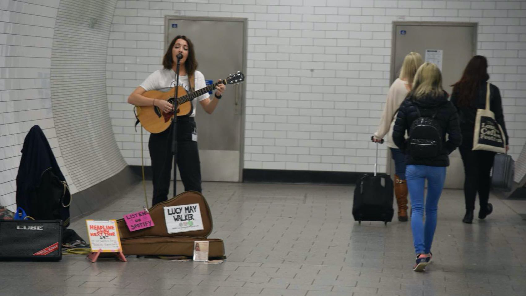 Lucy May Walker is a busker in action. The term busking is about license to sing. Often you'll need a busking permit from the local council to perform at a tube station in London.