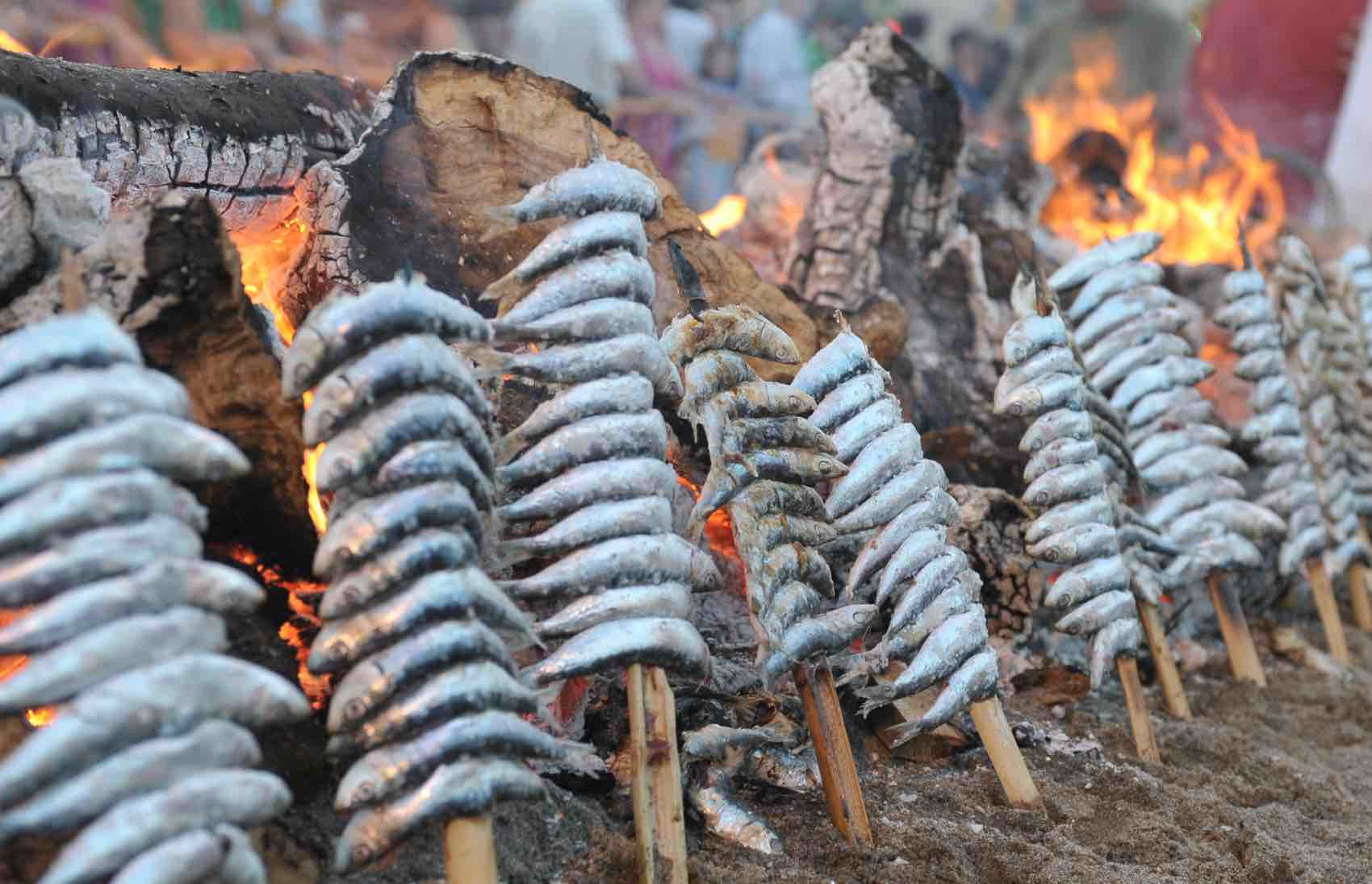 Espetos de sardinas: Sardines on a stick - roasting outdoor on the beach