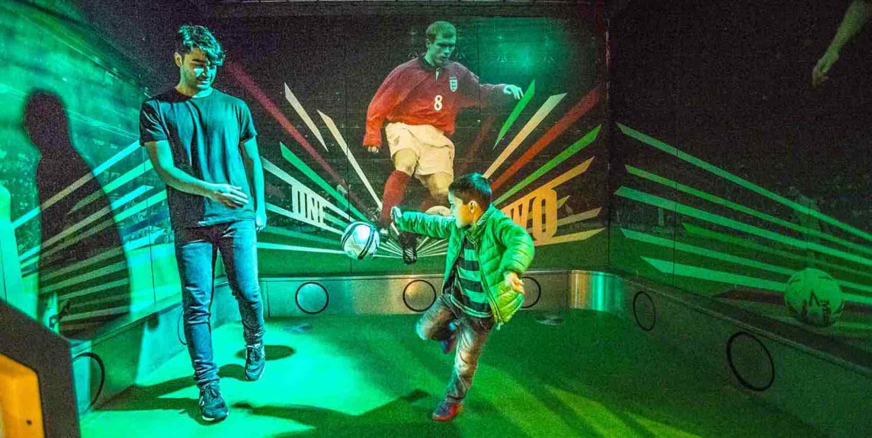 The National Football Museum. Father and son visiting the museum. Kicking a football and aiming at a goal.