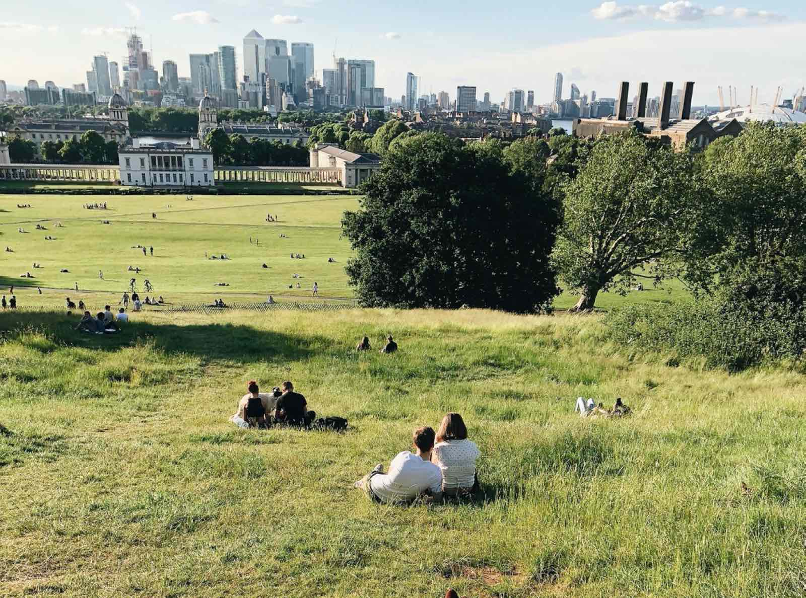 People sitting on the grass in Greenwich Park with a view of City skyscrapers in London.