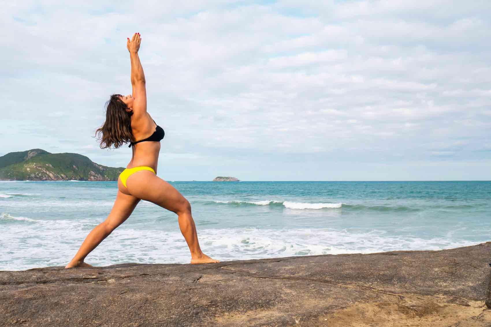 Woman gives a salute to the sun performing Yoga at Costa do Santinho beach in the island of Florianópolis, Santa Catarina, Brazil.