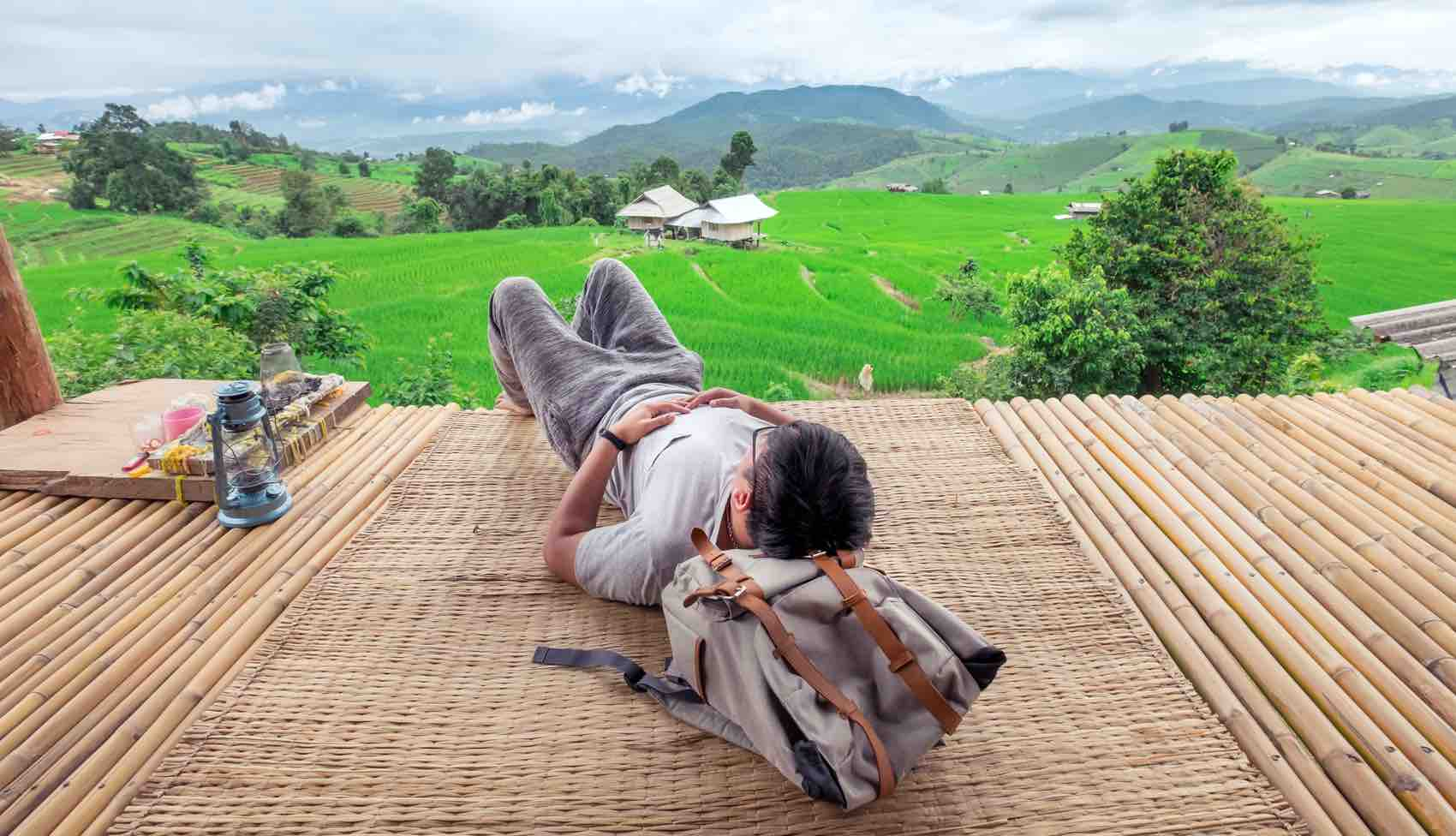 SLOW TRAVEL: A backpacker in Chiang Mai, the north of Thailand. Chill out and slow life in the open air balcony bamboo cottage looking out to beautiful rice terrace view.