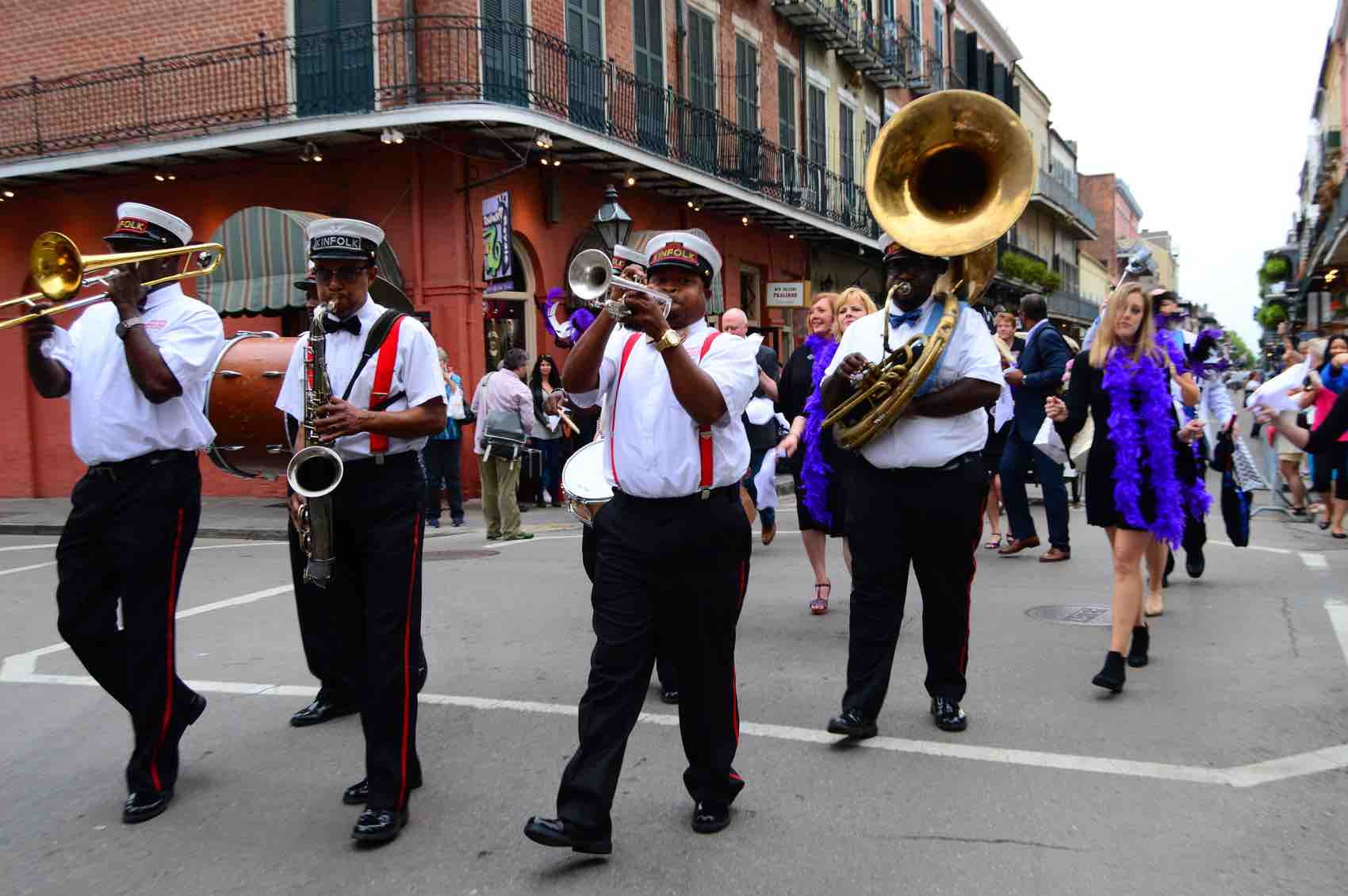 A group of musicians form a Second Line parade as they march through the French Quarter of New Orleans, Louisiana