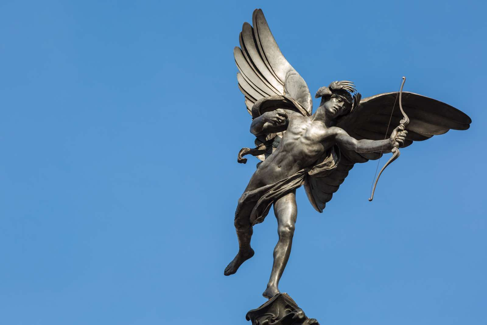 Famous statue of Eros, Amor, Cupid at Piccadilly Circus in London, on blue clear sky