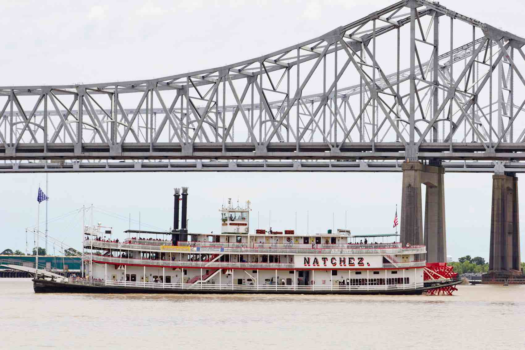 Natchez riverboat at the Crescent City Bridges on the Mississippi with tourists on board on one of its daily tours.
