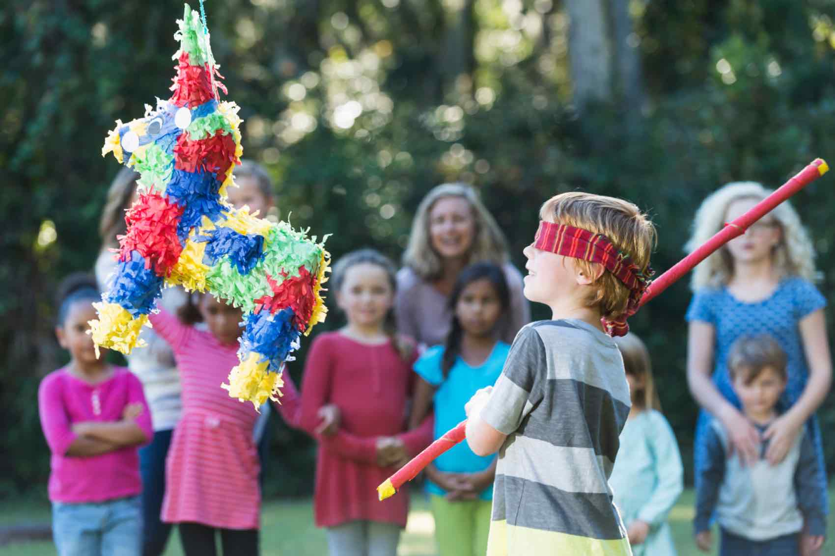Boy at party hitting pinata with stick in Mexico