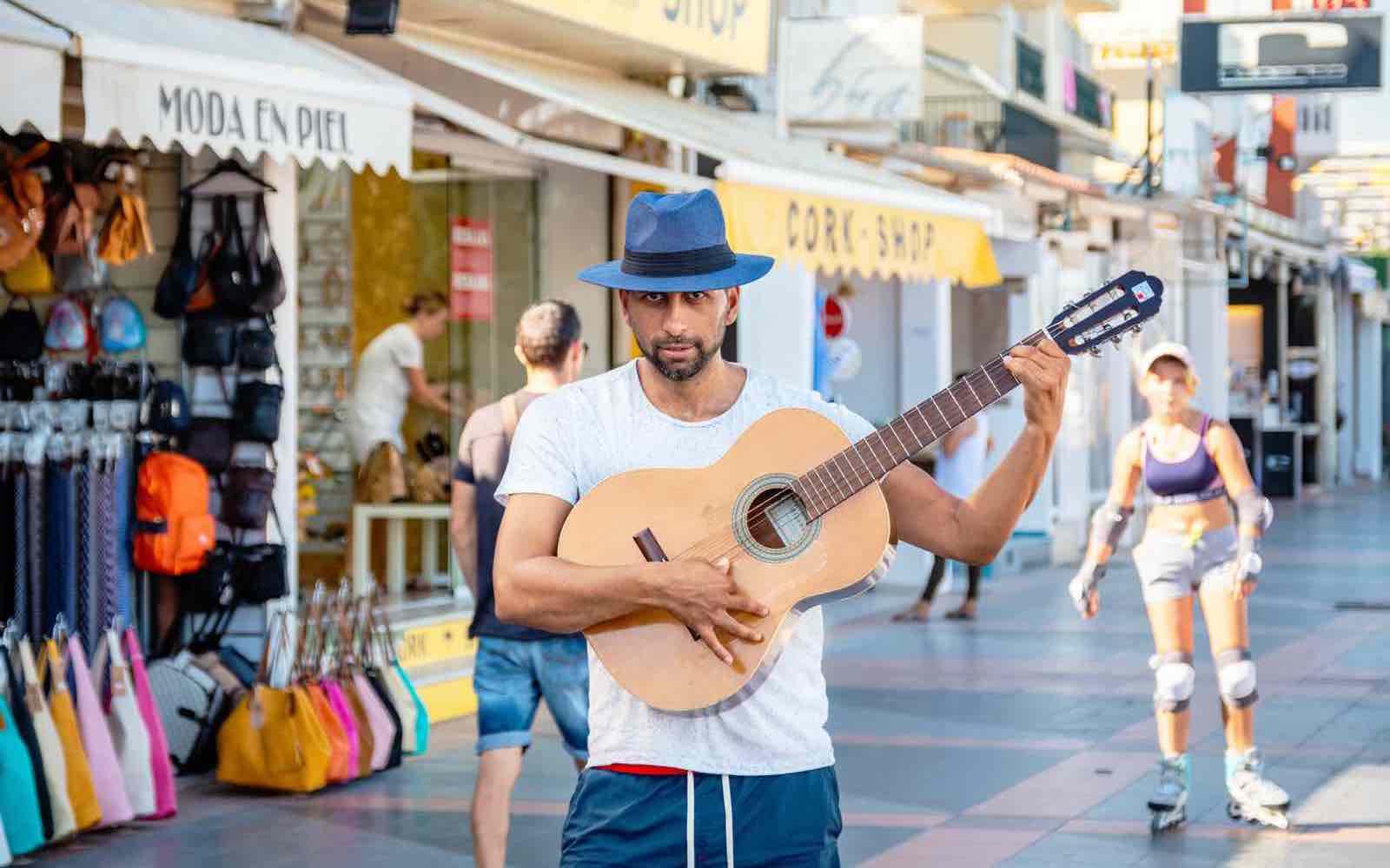 TORREMOLINOS, ANDALUSIA, SPAIN: Man playing the guitar on Carihuela promenade. Costa del Sol